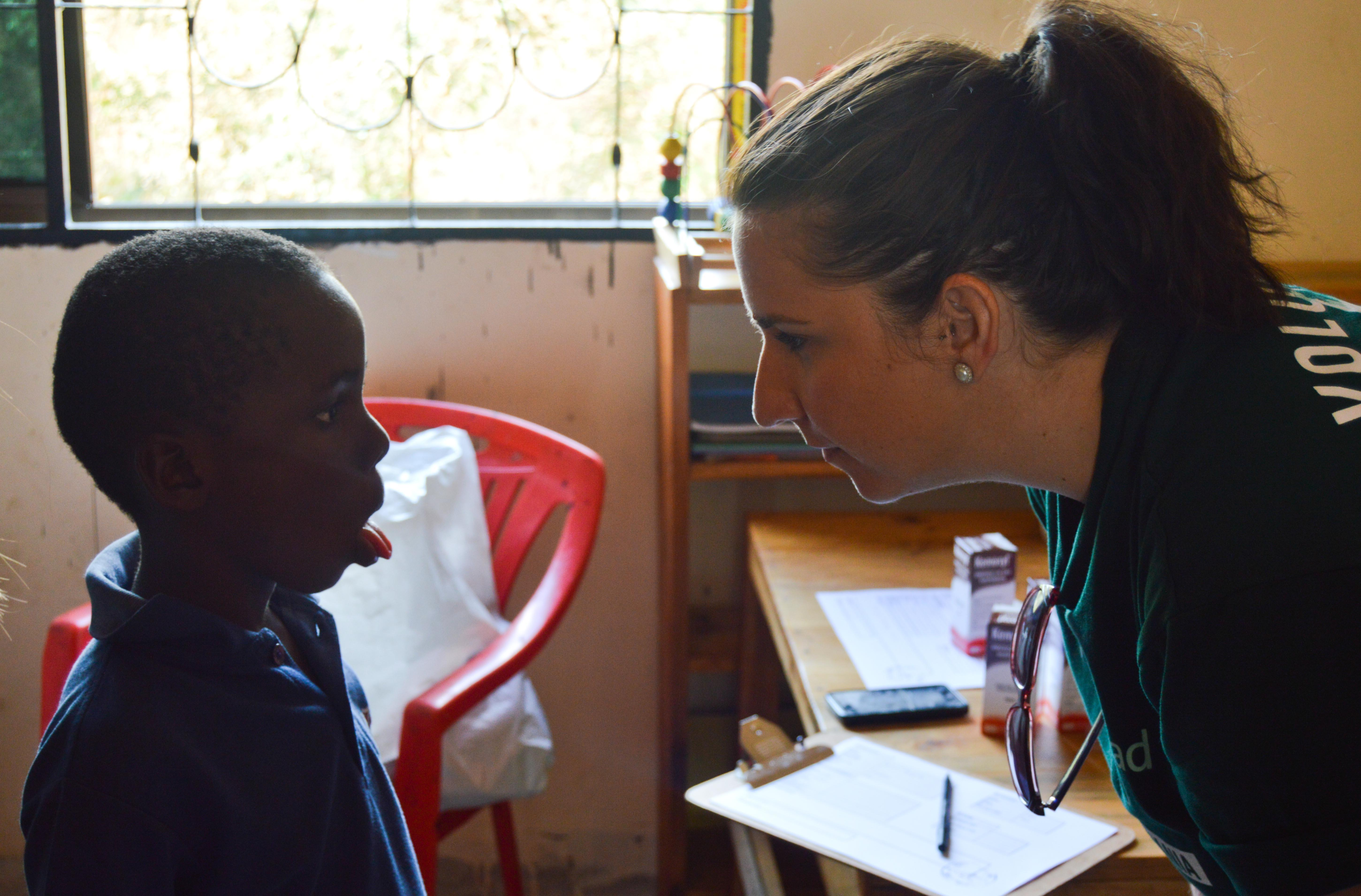 A young boy has his mouth and throat examined by a Projects Abroad Dentistry intern during an outreach in Tanzania.